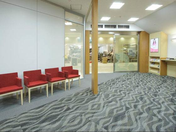 The Okazaki Shinkin Bank/【Waiting lounge】The space is accented with red chairs.