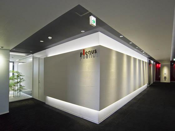 Plenus Company Limited/【Entrance area (Entrance - executive area)】Visitors are greeted in a space in which the corporate color of red leaves a strong impression
