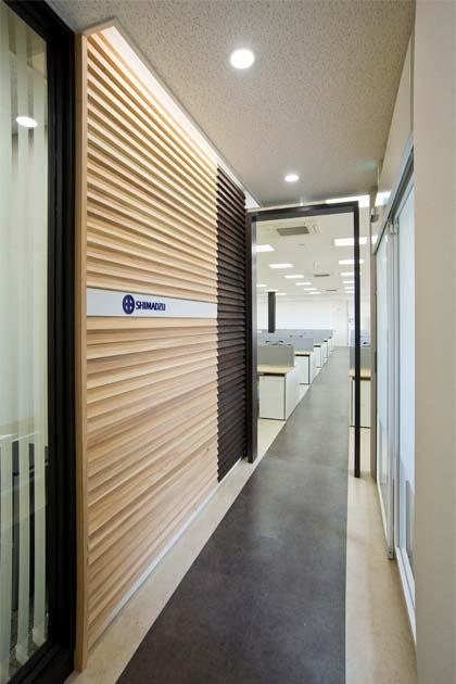 SHIMADZU LIMITED/【Entrance area】The boundary with the office is expressed with ornamental walls made of cedar grown in the prefecture