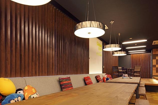 Nexon Co., Ltd./【Sofa area】Style consistency is provided by the use of black for ceilings and wood louvers for windows.