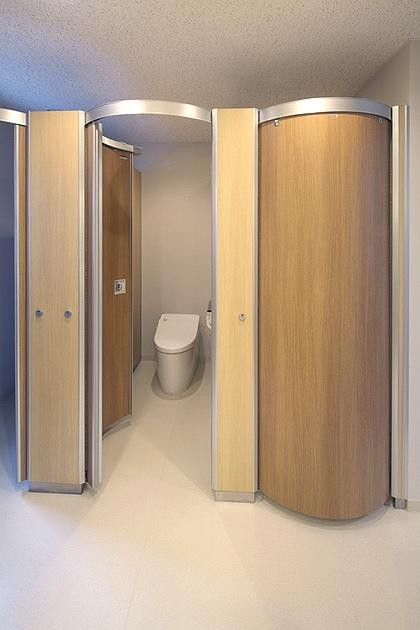 "FANCL Corporation/【Women's restroom】Tasteful wood-grain ""wavelet toilet booths"" are used."