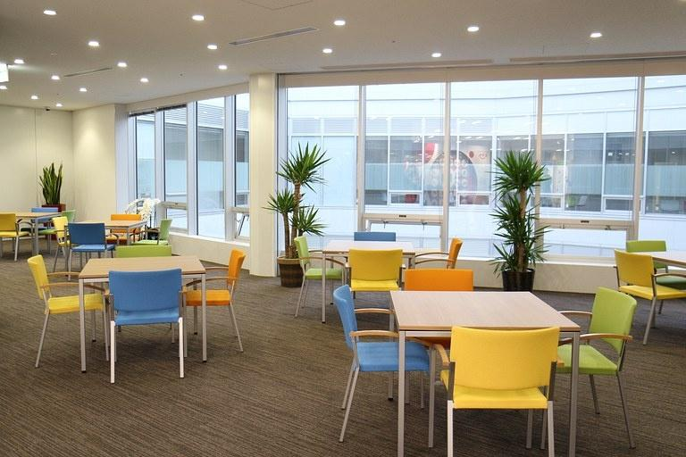 Ebara Foods Industry, Inc./【Entrance table seating】This visitor space uses assorted colors on the furniture and pillars.